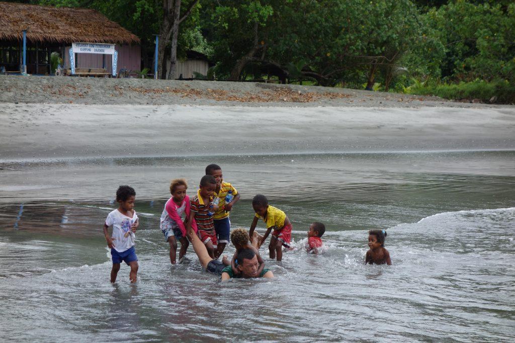 bocah-bocah sawendui bermain di bibir pantai yang menjadi perkarangan mereka.