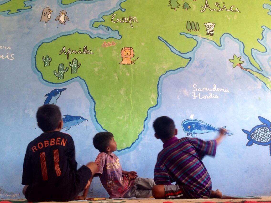 tiga anak pulau messah di taman bacaan pelangi sedang mengarang cerita yang gantian akan mereka bacakan kepada saya.