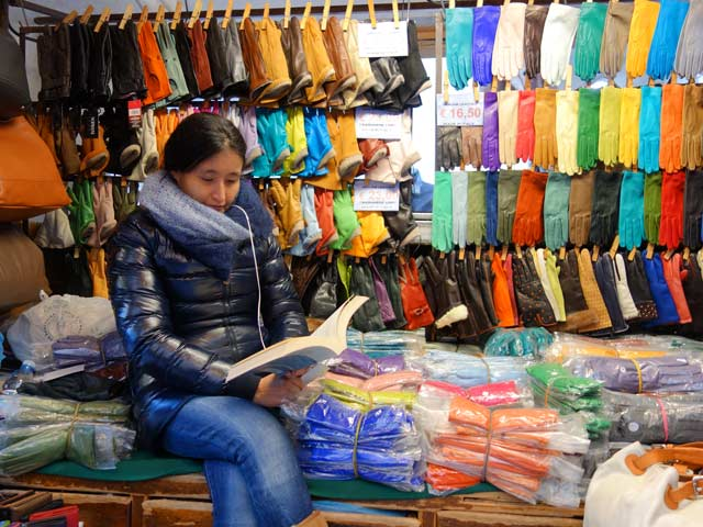 Penjualan kerajinan kulit di pasar Firenze tengah asyik membaca sambil menunggui dagangannya.